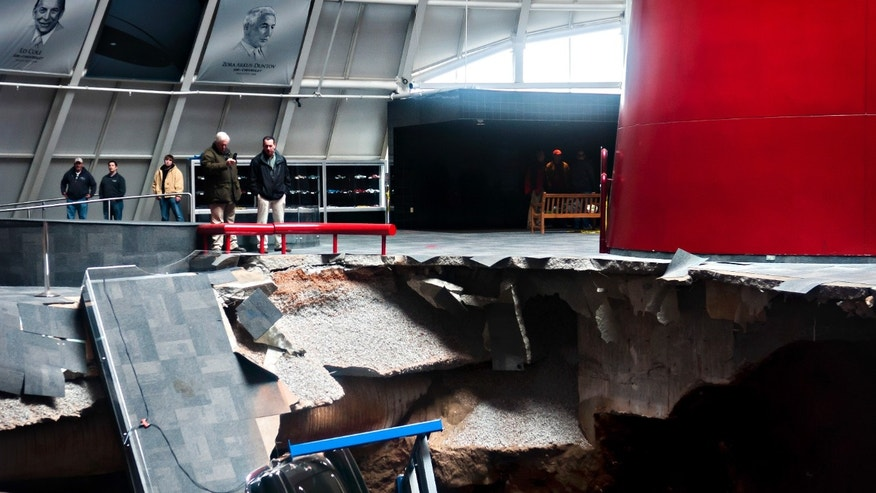 Officials view a sinkhole that opened up in the Skydome showroom, Wednesday, Feb. 12, 2014, at the National Corvette Museum in Bowling Green, Ky. Eight display cars were swallowed by the hole. (AP Photo/Daily News, Miranda Pederson)