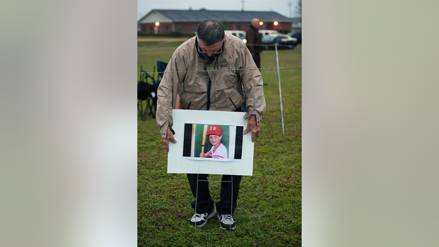 A friend of Jimmy Ryce puts up a photo of the boy at the Florida State Prison near Starke, Fla., just hours before the execution of Juan Carlos Chavez on Wednesday, Feb. 12, 2014. Chavez was executed Wednesday night for raping and killing 9-year-old Jimmy Ryce 18 years ago, a death that spurred the victim's parents to press nationwide for stronger sexual predator confinement laws and better handling of child abduction cases. (AP Photo/Phil Sandlin)