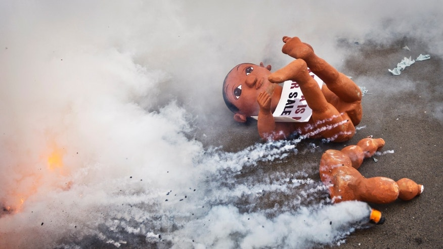"A giant mock baby used by anti-government protesters to represent what they claimed was the ""childish"" apathy of the Kenyan people and the need for the country to ""grow up"", lies abandoned on the street as demonstrators flee tear gas canisters fired by police exploding around them, in downtown Nairobi, Kenya Thursday, Feb. 13, 2014. Riot police in Nairobi fired tear gas to break up a demonstration making a variety of accusations against the Kenyan government including unemployment, corruption, poverty, impunity, and the failure to uphold rights contained in the constitution. (AP Photo/Ben Curtis)"
