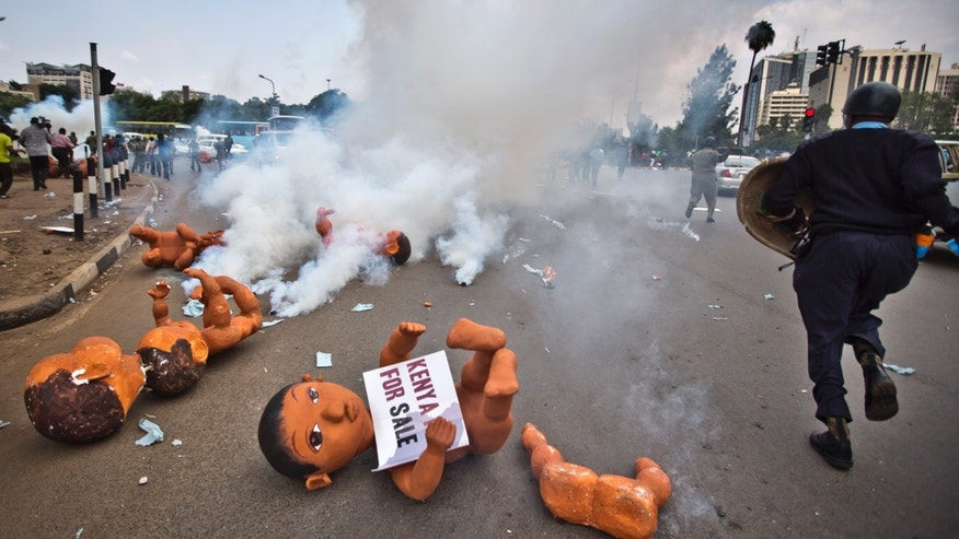 "A Kenyan riot policeman runs past giant mock babies abandoned in the street by anti-government protesters who said they represented the ""childish"" apathy of the Kenyan people and the need for the country to ""grow up"", as tear gas canisters fired by police explode around them, in downtown Nairobi, Kenya Thursday, Feb. 13, 2014. Riot police in Nairobi fired tear gas to break up a demonstration making a variety of accusations against the Kenyan government including unemployment, corruption, poverty, impunity, and the failure to uphold rights contained in the constitution. (AP Photo/Ben Curtis)"