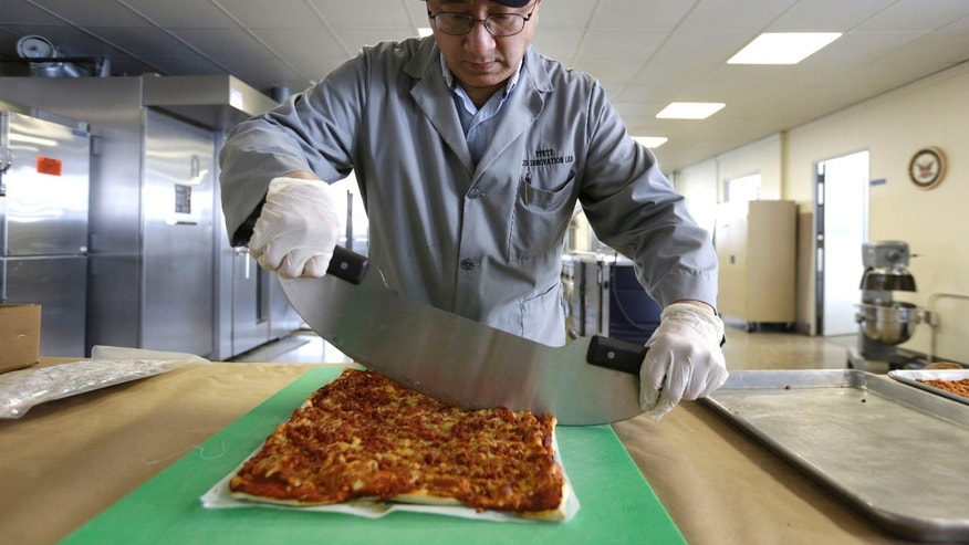 Feb. 6, 2014: Food technologist Tom Yang cuts a prototype pizza at the U.S. Army Natick Soldier Research, Development and Engineering Center, in Natick, Mass. Pizza is in development to be used in individual field rations known as meal ready to eat, or MREs. It has been one of the most requested options for soldiers craving a slice of normalcy in the battlefield and disaster areas. (AP Photo/Steven Senne)