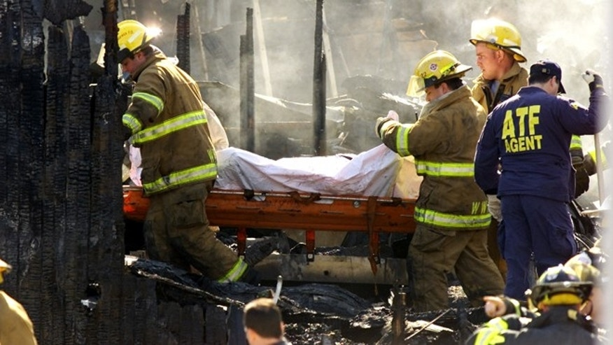 "Feb. 21, 2003: Firefighters carry the remains of a victim through the burnt wreckage of ""The Station"" nightclub in West Warwick, Rhode Island."