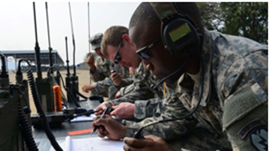 Staff Sgt. Adrian Little (front), Sgt. Jonathon Alexander (center) and Maj. Stewart Lindsay, 4th Brigade Combat Team (Airborne), 25th Infantry Division, conduct current airborne operations communications with five C-17 Globemaster III airplanes. (photo by Sgt. 1st Class Crista Mary Mack, U.S. Army)