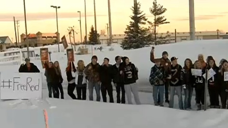 Feb. 18, 2014: About two dozen students waved signs and chanted outside Rogers High School Tuesday in support of Reid Sagehorn, an honor roll student and football team captain, suspended until April 22.