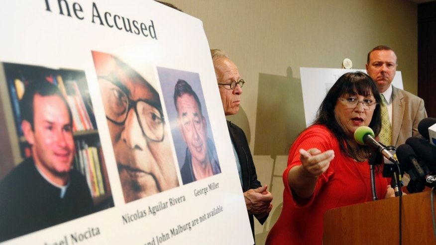 Esther Miller, a past victim of clergy abuse, points at her perpetrator, Michael Nocita, pictured far left, during a news conference announcing a $13 million settlement of behalf of 17 survivors who were sexually abused by five different perpetrators in the Archdiocese of Los Angeles, Wednesday, Feb. 19, 2014, in Los Angeles. Victims' attorneys, Jeff Anderson, left, and Anthony DeMarco, right, listen. (AP Photo/Nick Ut)