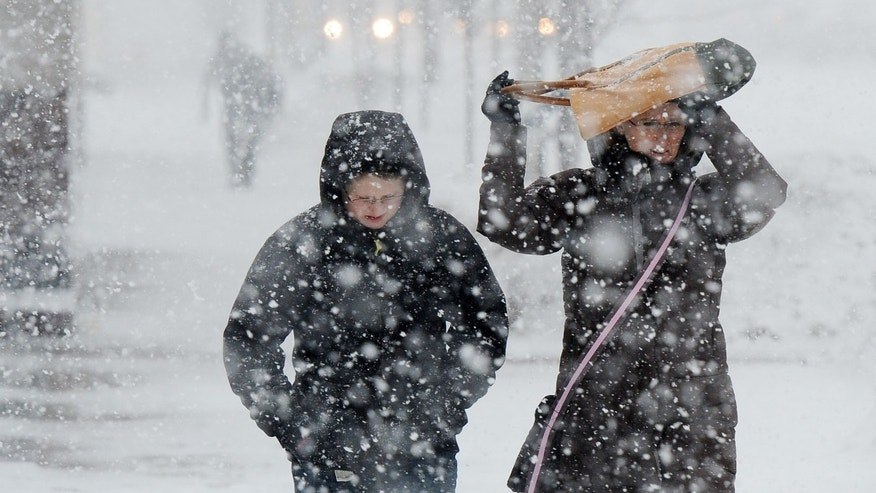 Tyler Traskos, 13, of Saline, walks with his mother Sandy as they cross N. Main St. in downtown Ann Arbor, Mich., on Thursday, Feb. 20, 2014.   A wintry mix of freezing rain, snow and sleet is falling across parts of Michigan's Lower Peninsula and blizzard conditions are forecast in parts of the Upper Peninsula. The National Weather Service says fog also is expected to create potential hazards on Thursday, followed by winds near 50 mph on Thursday night in the southeastern part of the state. Melting snow and rain could cause flooding in areas where temperatures are above freezing. (AP Photo/The Ann Arbor News, Melanie Maxwell)