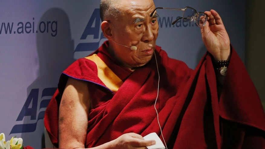 "Tibetan spiritual leader the Dalai Lama cleans his glasses before speaking at an event entitled: ""Happiness, Free Enterprise, and Human Flourishing"" Thursday, Feb. 20, 2014, at the American Enterprise Institute in Washington. (AP Photo/Charles Dharapak)"