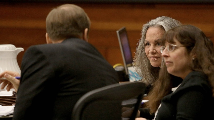 Defendant Pamela Phillip, center, listens to her attorney as opening arguments start in her trial Wednesday, Feb.19, 2014, in Tucson, Ariz.  Phillip is charged in the 1996 Tucson car bomb killing of her ex-husband   (AP Photo/Arizona Daily Star, A.E. Araiza) ALL LOCAL TV OUT; PAC-12 OUT; MANDATORY CREDIT