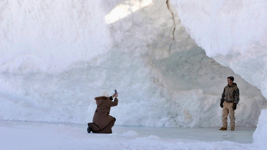 People take photos of the frozen waters and snow of Lake Michigan that have formed huge ice caves along the shore of northern Leelanau County, between Northport and Leland, Mich., on Wednesday, Feb. 19, 2014. Sub-zero temperatures in late December through mid-January, along with strong winds and heavy snowfall, created the huge ice ridges several hundred feet from shore. (AP Photo/John L. Russell)