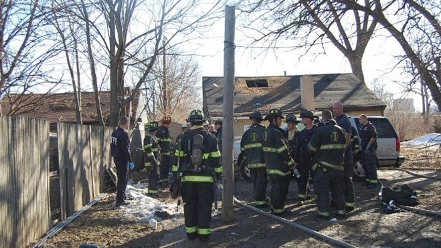 Feb. 22, 2014: This photo provided by the Indianapolis Fire Department, fire and emergency personnel look over the scene of a fire in Indianapolis.
