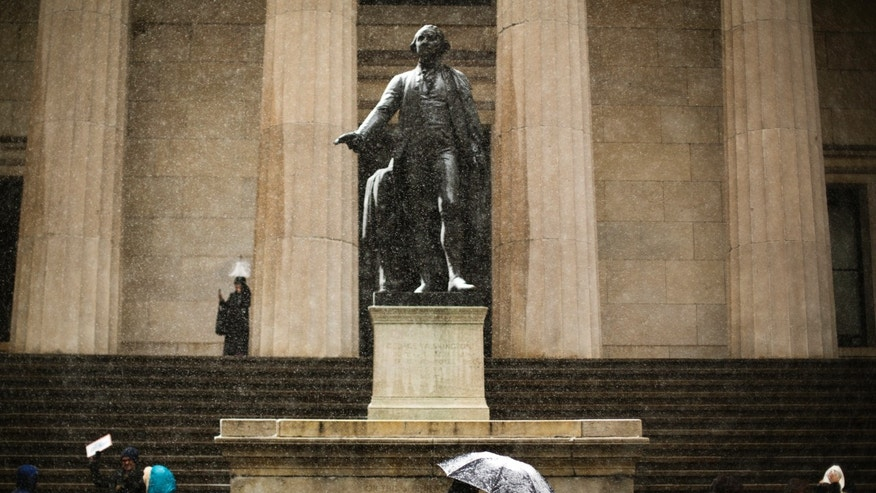 Commuters walk past a statue of George Washington on the steps of Federal Hall as they walk through heavy snow flurries in New York.