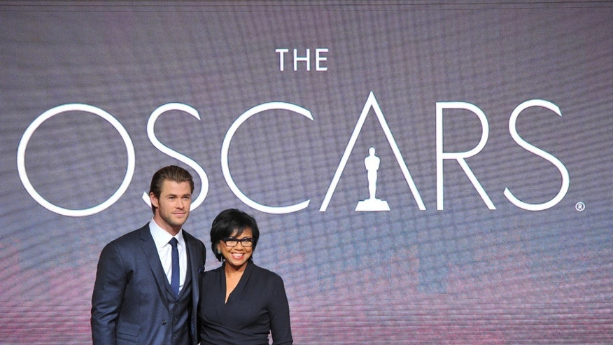 FILE - In this Thursday, Jan. 16, 2014 file photo, Chris Hemsworth, left, and President of the Academy Cheryl Boone Isaacs pose at the 86th Academy Awards nomination ceremony in Beverly Hills, Calif. Isaacs has become the third female Academy of Motion Picture Arts and Sciences president and the first ever African-American head of the organization. The 86th Annual Academy Awards will take place on Sunday, March 2,  2014, at the Dolby Theatre in Los Angeles.   (Photo by Vince Bucci/Invision/AP, File)