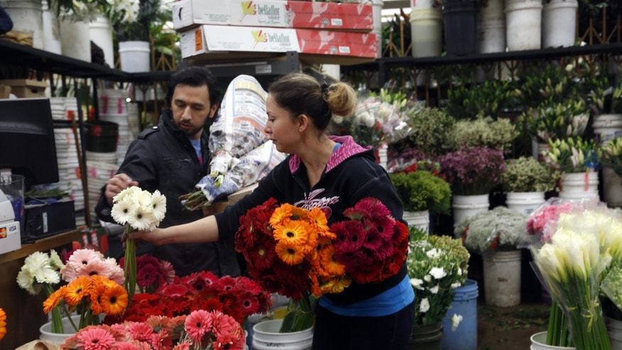 FILE - In this Feb. 14, 2014, photo, buyer Steve Moren, left, examines flowers for purchase for his girlfriend for Valentine's Day, at the Flower Market in Los Angeles. The Conference Board releases the Consumer Confidence Index for February, on Tuesday, Feb. 25, 2014. (AP Photo/Nick Ut, File)