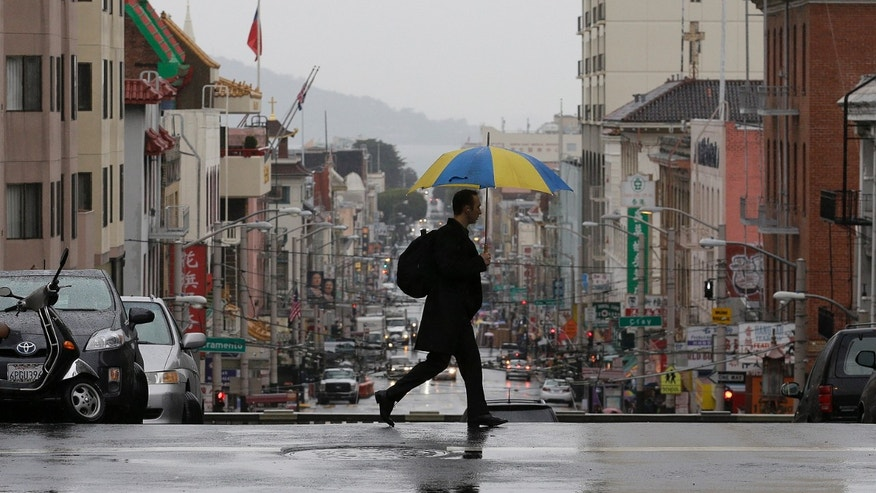 A man crosses Stockton Street in San Francisco, Wednesday, Feb. 26, 2014. The first storm was expected to hit Northern California Wednesday morning and move down the coast, dumping a half-inch to an inch in southern areas late in the day, forecasters said. (AP Photo/Jeff Chiu)