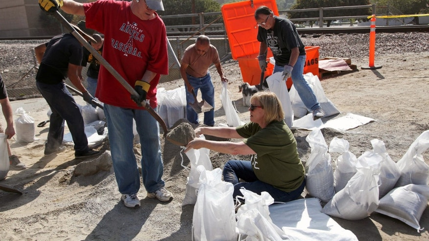 Mark and Barbara Albanese fill sand bags to protect their home from the possible flooding ahead of an expected rain storm in Azusa,Calif. on Tuesday, Feb 25, 2014. In anticipation of the first substantial winter storm system in drought-stricken California, residents of foothill communities picked up sandbags at fire stations and city yards to protect their homes on Tuesday. (AP Photo/Nick Ut )