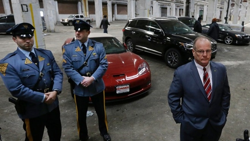 Feb. 27, 2014: Superintendent of the New Jersey State Police, Colonel Joseph R. Fuentes, right, stands with troopers near recovered stolen cars in a warehouse in Bayonne, N.J. Earlier acting New Jersey Attorney General, John Jay Hoffman announced that nearly three dozen people were arrested or charged in an auto theft ring that used tactics including carjackings in New York and New Jersey to help feed a demand for luxury sport utility vehicles in West Africa. Hoffman said many of the more than 160 vehicles were recovered in the 10-month investigation had been returned to owners or insurance companies. (AP/Mel Evans)