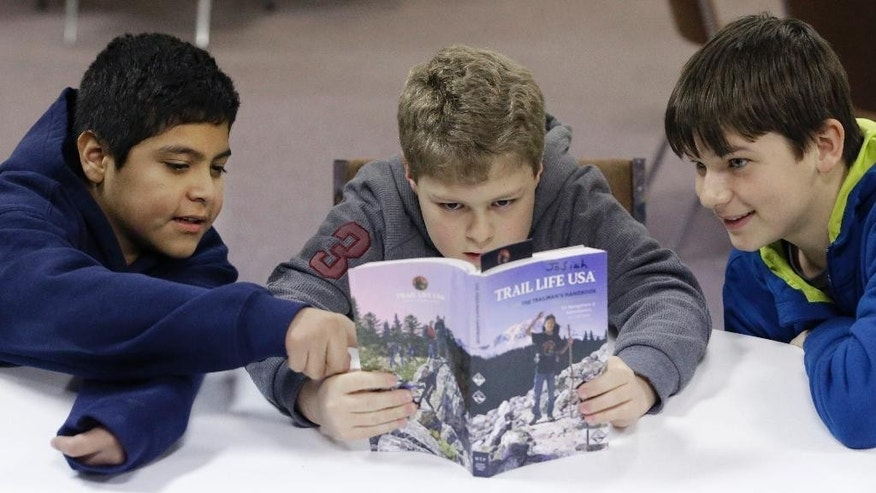 In this Tuesday, Feb. 4, 2014 photo, from left, Erick Izquierdo, Josiah Spear, 12, and Cole McSorley, 12, look at a Trail Life handbook during a gathering of members in North Richland Hills, Texas. Trail Life USA says it has established units in more than 40 states, mostly from Boy Scouts and parents who feel the century-old organization has lost its way. (AP Photo/LM Otero)