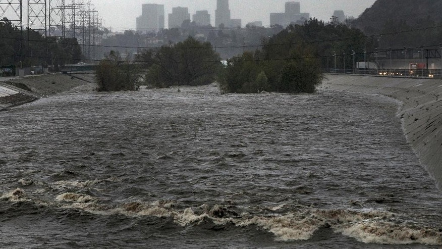 With the Los Angeles skyline in the background, the Los Angeles River flows Friday, Feb. 28, 2014. Two men and their dogs were rescued earlier from the swift waters of the LosAngelesRiver. A few miles downriver, another man was pulled out and carried to safety. Even with rainfall totals exceeding six inches in some places Friday, the powerful Pacific storm did not put a major dent in a drought that is among the worst in recent California history. (AP Photo/Damian Dovarganes)