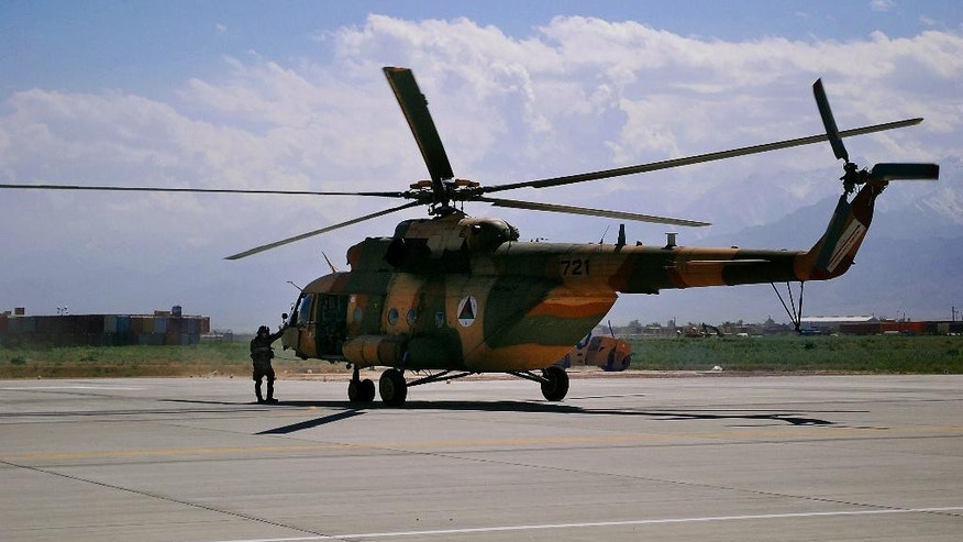FILE - This May 13, 2013 file photo shows a Mi-17 helicopter used by the Afghan Air Force at Bagram Air Field in Afghanistan. Yuri Borisov's performance on a lucrative U.S. military contract was dismal. Cost overruns. Blown deadlines. Forged paperwork. Yet that didn't keep the Russian entrepreneur from winning more business with the Department of Defense, according to interviews and documents obtained by The Associated Press. Borisov, who specializes in refurbishing Russian Mi-17 helicopters, had an ally in Bert Vergez, an Army colonel who ran an obscure DOD acquisition office in Huntsville, Ala. (AP Photo/Kristin M. Hall, File)