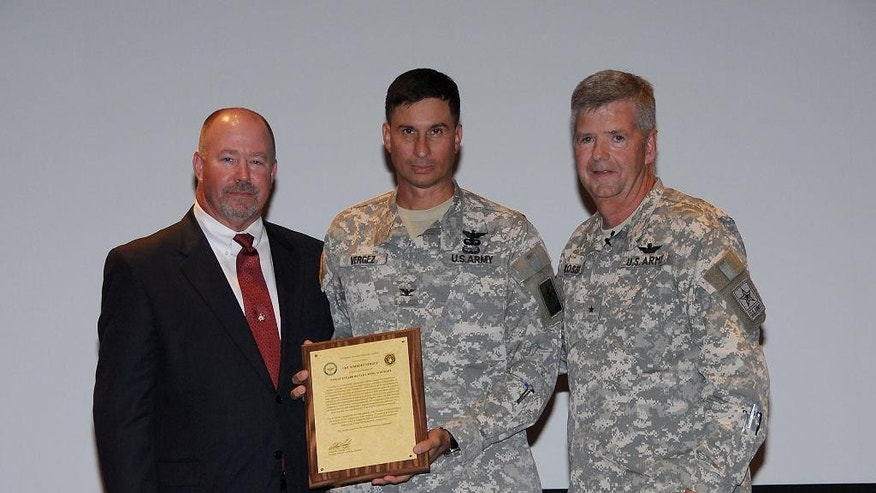 This handout photo provided by the US Army, taken in Jan. 2010, shows retired Army Col. Bert Vergez, center, receiving his charter to manage the Project Office for Non-Standard Rotary Wing Aircraft (NSRWA), established in January 2010, from the Program Executive Officer for Aviation, now Maj. Gen. William Crosby, right, and Randy Harkins, former deputy project manager NSRWA. The relationship between the two men is at the heart of a criminal probe into why the Huntsville office Vergez once commanded kept dealing with Yuri Borisov despite an alarming catalogue of problems. The case is a glimpse into the labyrinth of military procurement, where even today, Borisov's companies, AviaBaltika Aviation and Saint Petersburg Aircraft Repair Company, remain technically eligible for federal contracts Although the inspector general's audit recommended the Army take steps to debar or suspend them, no such action has been taken more than a year later. (AP Photo/US Army)