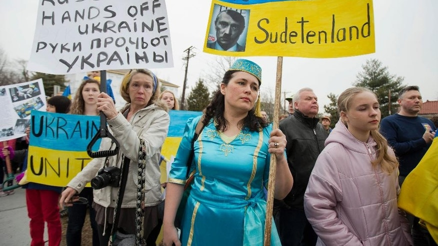 "Velida Kent, second form right, whose family originated from Crimea, wears her native Crimean Tatar outfit, during a protest rally in front of the Russian embassy, in Washington, Sunday, March 2, 2014. Igniting a tense standoff, Russian forces surrounded a Ukrainian army base Sunday just as the country began mobilizing in response to the surprise Russian takeover of Crimea. Outrage over Russia's tactics mounted in world capitals, with U.S. Secretary of State John Kerry calling on President Vladimir Putin to pull back from ""an incredible act of aggression."" (AP Photo/Manuel Balce Ceneta)"