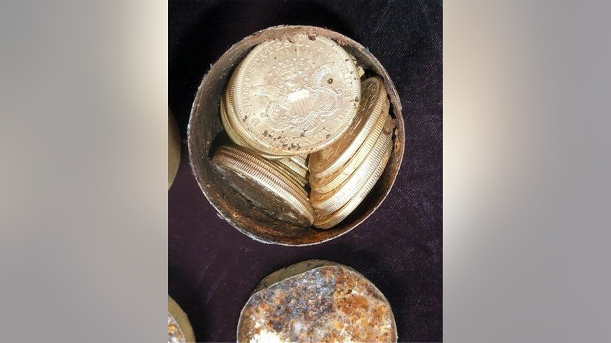 This image provided by the Saddle Ridge Hoard discoverers via Kagin's, Inc., shows one of the six decaying metal canisters filled with 1800s-era US gold coins unearthed in California.