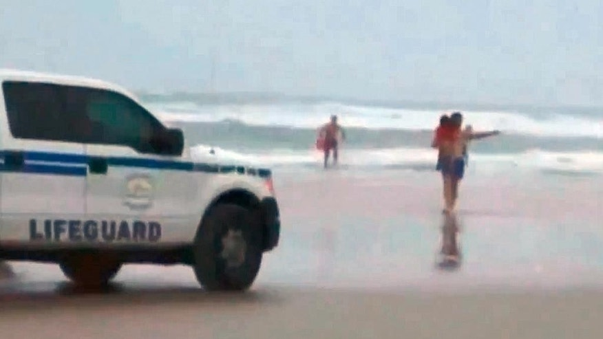 In this image made from video and released by Simon Besner, lifeguards rescue children from a minivan that their mother drove into the Atlantic, Tuesday, March 4, 2014 in Daytona Beach, Fla.  Ebony Wilkerson, 31, a pregnant South Carolina woman who drove a minivan carrying her three young children into the ocean surf off Florida had talked about demons before leaving the house, according to her sister who worriedly called police, officials said during a news conference Wednesday.  Bystanders and officers helped pull Wilkerson and her children, ages 3, 9 and 10,  from their minivan. The children were turned over to welfare authorities. The Volusia County Sheriff's Office says Wilkerson was undergoing a mental evaluation. (AP Photo/Simon Besner)