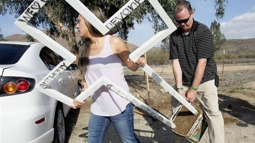 Mercedez Devaney, 24 and her father take down one of the roadside memorial crosses for her brother.