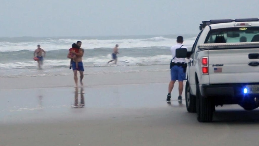 FILE - In this March 4, 2014 file image made from video, a lifeguard carries one of the three children rescued from a minivan that their mother, Ebony Wilkerson, drove into the Atlantic in Daytona Beach, Fla. Wilkerson as charged Friday with attempted first-degree murder and aggravated child abuse, though she has denied trying to harm anyone, authorities said. (AP Photo/Simon Besner, File) NO SALES
