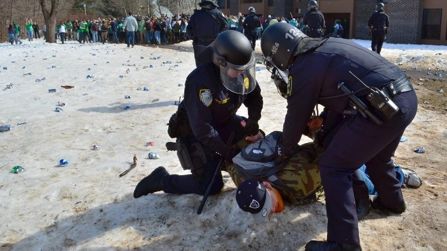 "Police detain a participant in the pre-St. Patrick's Day ""Blarney Blowout"" near the University of Massachusetts in Amherst, Mass. on Saturday, March 8, 2014. According to the Amherst police department, four police officers were hurt as they worked to disperse hundreds of unruly students who were throwing beer cans and bottles at police on Saturday as large crowds gathered at the off-campus apartment complex. Police in riot gear arrested 35 at the event. (AP Photo/The Republican, Robert Rizzuto)"