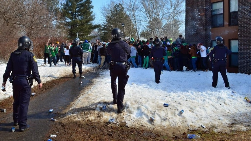 "Police surround participants in the pre-St. Patrick's Day ""Blarney Blowout"" near the University of Massachusetts in Amherst, Mass. on Saturday, March 8, 2014. According to the Amherst police department, four police officers were hurt as they worked to disperse hundreds of unruly students who were throwing beer cans and bottles at police on Saturday as large crowds gathered at the off-campus apartment complex. Police in riot gear arrested 35 at the event. (AP Photo/The Republican, Robert Rizzuto)"