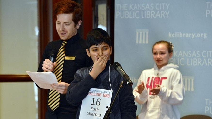 "March 8, 2014: Kush Sharma, center, reacts after spelling ""definition"" to win the Jackson County Spelling Bee in the 29th round at the Central Library, as Sophia Hoffman, right, looks on, in Kansas City, Mo. Two weeks ago, the bee ran out of words after the two eliminated 23 other contestants and went another 47 rounds against each other. (AP Photo/The Kansas City Star, Jill Toyoshiba)"