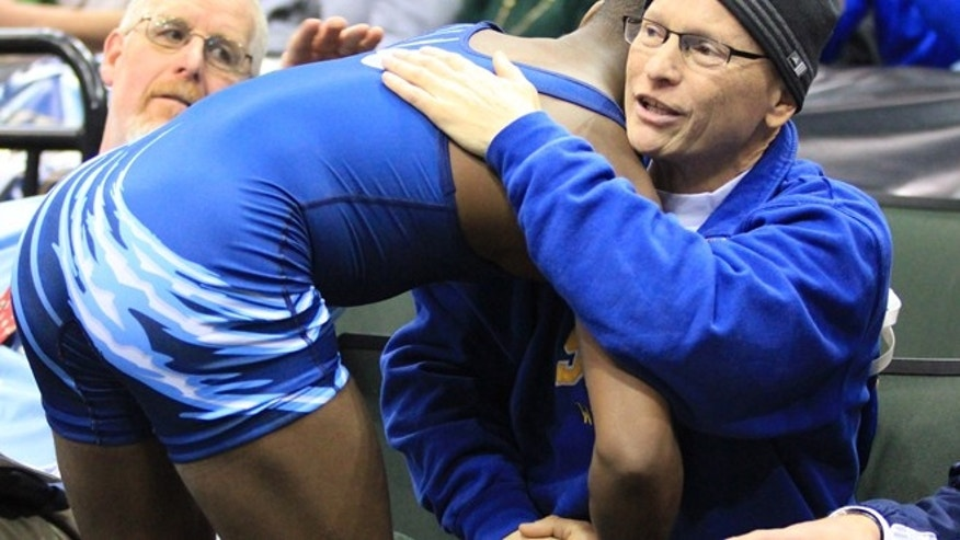March 1, 2014: Minnesota wrestler Malik Stewart hugs Steve McKee moments after losing his Class 3A 120-pound high school wrestling title match to McKee's son in St. Paul, Minn. Stewart's gesture to the terminally ill father of the opponent who had just beaten him captured the hearts of fans at Xcel Energy Center.