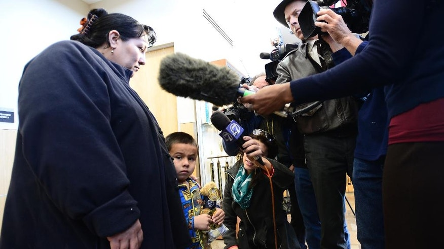 Allan Chavarria-Rodriguez, 4, snuggles next to his mother, Marta Rodriguez at the police station in Brighton, Colo., Wednesday, March 12, 2014. Police say Chavarria-Rodriguez was found unharmed after Ryan Stone abandoned an SUV he had allegedly stolen in Longmont, Colo.  (AP Photo/The Daily Camera, Mark Leffingwell) NO SALES