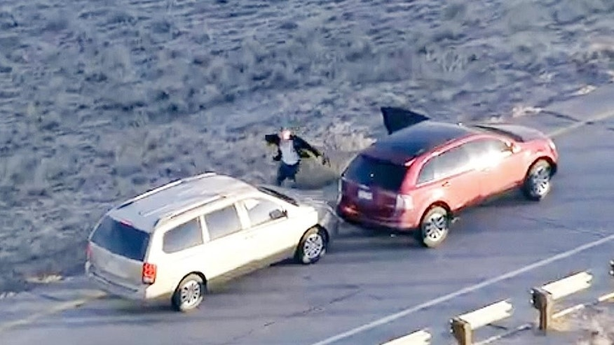 In this image taken from video provided by CBS-4 TV Denver, Ryan Stone, abandons an stolen SUV, right, with a 4-year-old child inside and steals a car, left, during a high speed chase in the Denver Metro Area, Wednesday, March 12, 2014. Stone was arrested after fleeing another vehicle, slipping on ice in a shopping center and failing to clear a fence Wednesday. (AP Photo/Courtesy CBS-4 TV)