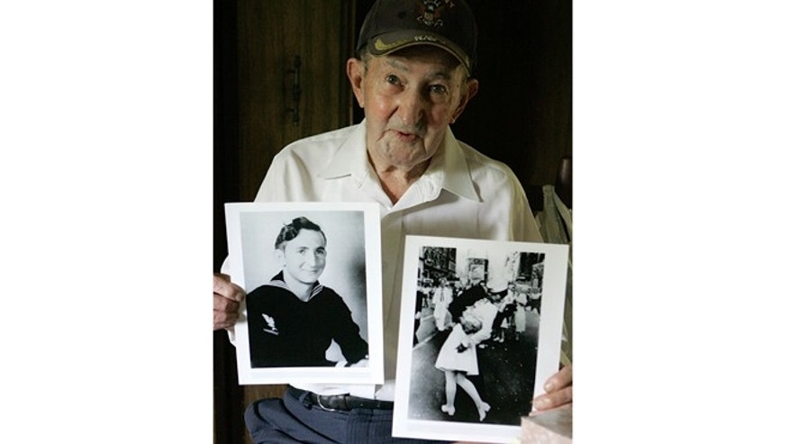July 31, 2007: In this photo, Glenn McDuffie holds a portrait of himself as a young man, left, and a copy of Alfred Eisenstaedt's iconic Life magazine shot of a sailor, who McDuffie claims is him, embracing a nurse in a white uniform in New York's Times Square, at his Houston home.