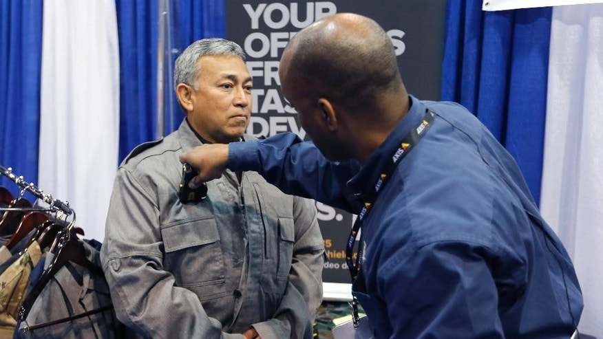 G Squared Consulting Partner Gregory Williams, right, uses an  Electroshock weapon on CEO Alex Solis, who is protected by their specialized clothing that is resistant to Electroshock, at the 8th annual Border Security Expo, Tuesday, March 18, 2014 in Phoenix. The two day event will feature panel discussions, sharing intelligence, and exhibitors displaying high-tech wares aimed at securing lucrative government contracts and private sales. (AP Photo/Matt York)