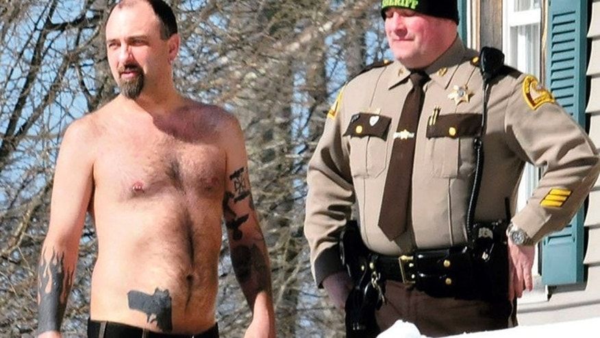 March 18: Michael Smith, left, stands beside a Somerset County Sheriff deputy outside his home in Norridgewock, Maine.