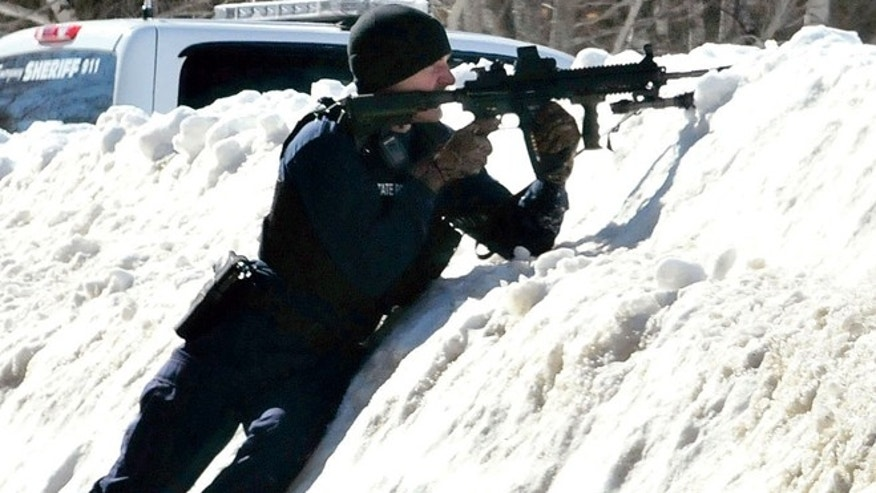 March 18: A trooper trains his rifle toward the home of Michael Smith in Norridgewock, Maine.