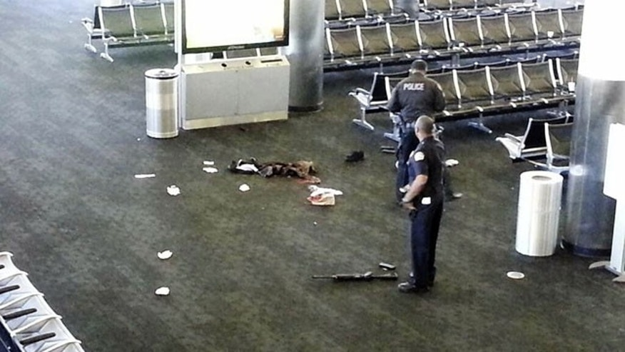 November 1, 2013: Police officers stand near a weapon at the Los Angeles International Airport after a gunman opened fire in the terminal, killing one person and wounding several others. (AP)