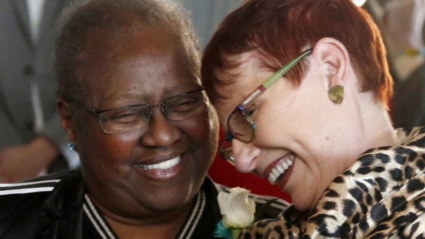 FILE - In this Nov. 27, 2013 file photo, Vernita Gray, left, and Patricia Ewert, smile after their wedding ceremony in Chicago. They were the first couple to be married after the gay marriage law was signed by the governor. Because Gray was terminally ill, they were issued an expedited marriage license before the state's gay marriage law took effect in June 2014. A family friend says Vernita Gray died late Tuesday, March 18, 2014, of cancer. She was 65. (AP Photo/Charles Rex Arbogast, File)