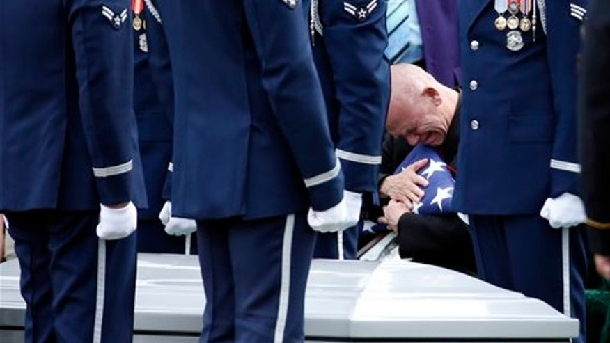 March 21, 2014: Steven Woods grieves as he hugs a flag during a group burial service for his father Army Staff Sgt. Lawrence Woods, and Air Force Capt. Valmore W. Bourque, Air Force 1st Lt. Robert G. Armstrong, Air Force Staff Sgt. Ernest J. Halvorson, Air Force Staff Sgt. Theodore B. Phillips, Air Force Airman 1st Class Eugene Richardson, Army Pfc. Charles P. Sparks  at Arlington National Cemetery in Arlington, Va.