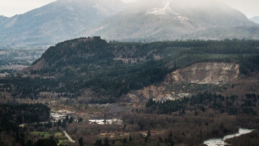 A wide aerial view shows the extensive damage of the landslide after taking out a chunk of earth from the side of the hill facing the Stillaguamish River, and down into the State Route 530, on the left, between the cities of Arlington and Darrington, on Saturday, March 22, 2014. Search and rescue operations are underway for survivors. (AP Photo/ The Seattle Times, Marcus Yam )