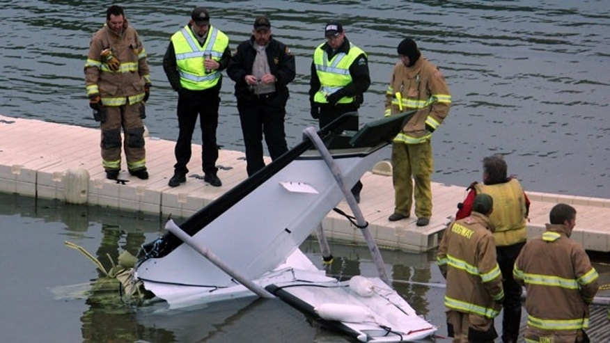 March 22, 2014: This photo provided by the Ouray County Plaindealer shows rescue personnel examining the tail second of a plane after it was recovered from the Ridgeway Reservoir south of Montrose. Colo. The plane believed to be carrying five people crashed into a reservoir in southwestern Colorado and authorities say all are feared dead. (AP Photo/Ouray County Plaindealer, Patrick Moore)