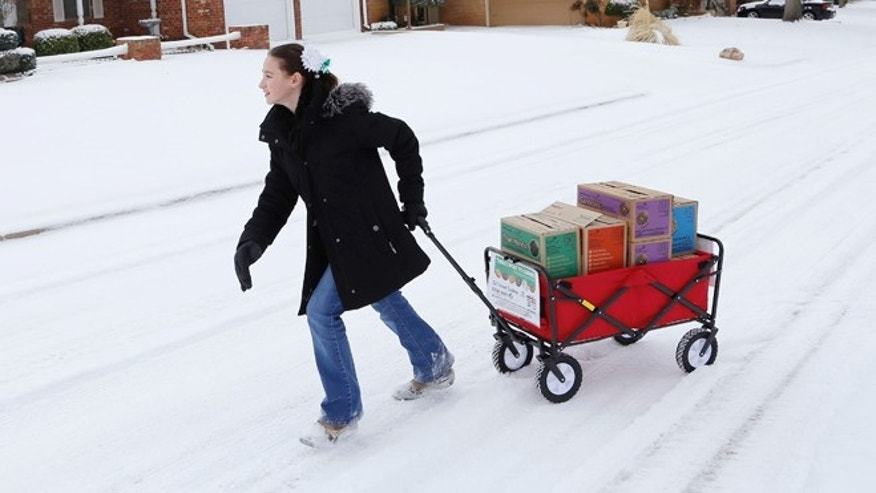 Feb. 6: Katie Francis pulls her wagon full of boxes of cookies in the snow through a neighborhood in Warr Acres selling cookies in Oklahoma City.