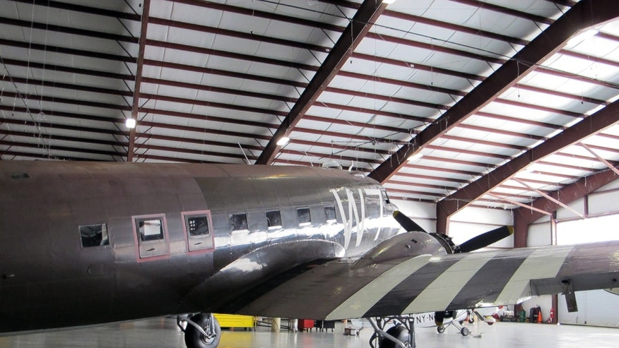 This photo taken March 6, 2014, shows a World War II-era Douglas C-47, housed at the National Warplane Museum in Geneseo, N.Y., and pilot Naomi Wadsworth. At the invitation of the French government,  the airplane will return to France in June to participate in celebrations marking the 70th anniversary of the D-Day invasion of Normandy. The airplane, known as Whiskey 7 because of its markings, is one of the original troop carriers that dropped paratroopers in advance of the amphibious invasion. In June it will recreate its role and drop paratroopers over the original drop zone in Sainte-Mere-Eglise. (AP Photo/Carolyn Thompson)