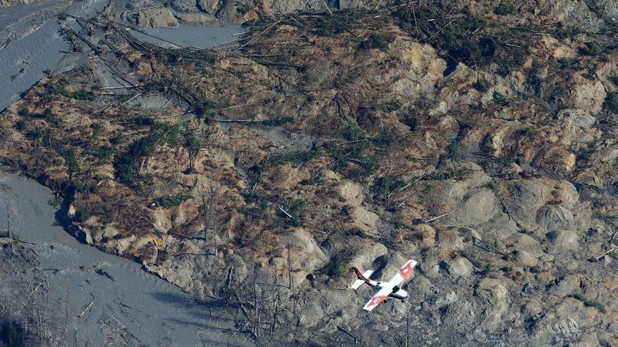 A Civil Air Patrol plane flies over the massive mudslide that killed at least eight people and left dozens missing as shown in this aerial photo, Monday, March 24, 2014, near Arlington, Wash. The search for survivors grew Monday raising fears that the death toll could climb far beyond the eight confirmed fatalities. (AP Photo/Ted S. Warren)