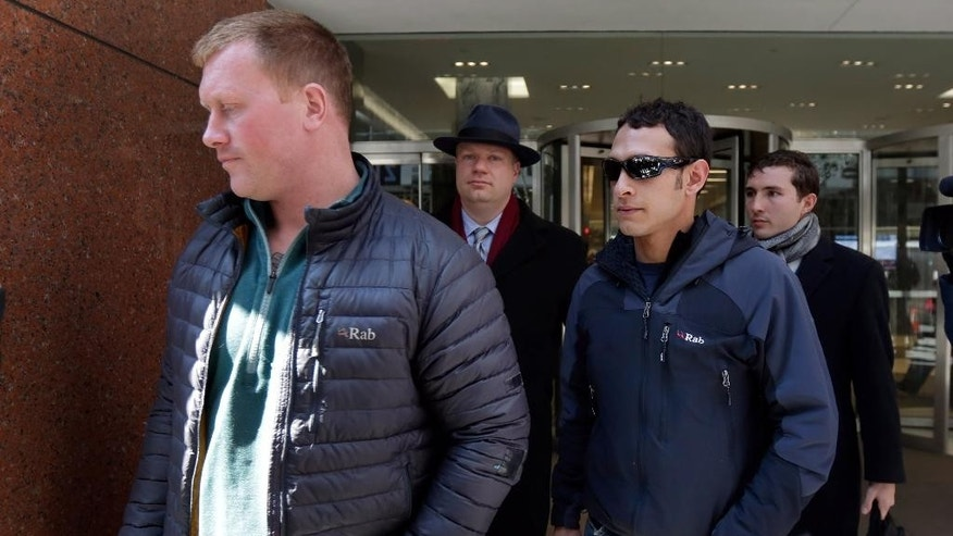 "James Brady, and Andrew Rossig, foreground left and right, two parachutists who jumped from One World Trader Center in September 2013, are accompanied by attorneys Timothy Parlatore, background left and Andrew Mancilla, to surrender to police, in New York,  Monday, March 24, 2014. Monday's arrests come eight days after a 16-year-old was arrested on charges of climbing up to the top of the nation's biggest skyscraper. Police had no immediate information on Monday's arrests. They had said they were looking for two parachutists seen floating near the building Sept. 30. The defense attorneys say  three accused jumpers and an alleged accomplice on the ground are expecting to face felony burglary charges. The attorneys say the defendants are experienced BASE jumpers, the acronym stands for ""building, span, antenna, earth."" The lawyers say the men took care to keep from endangering anyone. (AP Photo/Richard Drew)"