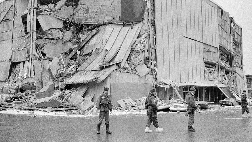File - In this March 28, 1964 file photo, with the city under martial law, soldiers patrol a downtown street in Anchorage, Alaska. In bacground is the wreckage of the five-story Penney store at Fifth Avenue and D Street. North America's largest earthquake rattled Alaska 50 years ago, killing 15 people and creating a tsunami that killed 124 more from Alaska to California. The magnitude 9.2 quake hit at 5:30 p.m. on Good Friday, turning soil beneath parts of Anchorage into jelly and collapsing buildings that were not engineered to withstand the force of colliding continental plates. (AP Photo/File)