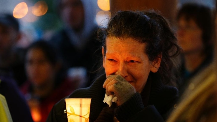 Teresa Welter cries as she holds a candle, Tuesday, March 25, 2014, at a candlelight vigil in Arlington, Wash., for the victims of a massive mudslide that struck the nearby community of Oso, Wash., on Saturday, killing at least 16 people and leaving dozens missing. (AP Photo/Ted S. Warren)